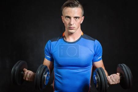 Athletic  young male fitness model holds the dumbbell with light isolated on dark background.