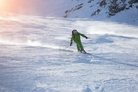 Attractive Male Skier Rides down the Slope on A Sunny Day