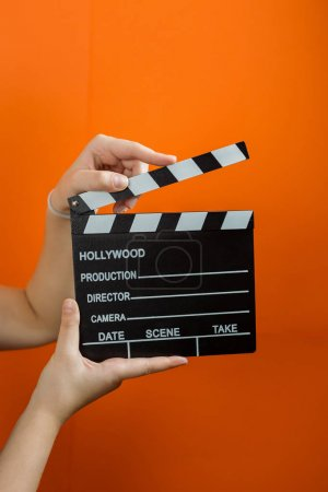 movie clapper on orange background, cinema concept