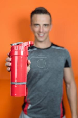 Portrait of a  body builder holding a scoop of protein mix in gym
