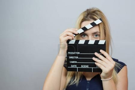 Young woman in action, holding clapperboard. Cinema concept