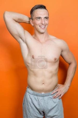 Athletic shirtless young male fitness model posing in studio on orange background