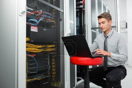 Photo pour Homme d'affaires jeune avec ordinateur portable de travail au datacenter - image libre de droit