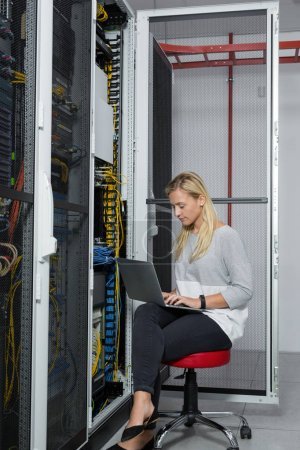 Photo for Portrait of technician working on laptop in server room - Royalty Free Image