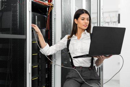 Photo pour Portrait de technicien travaillant sur ordinateur portable dans la salle des serveurs - image libre de droit