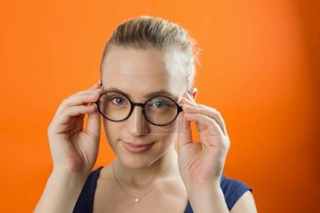 Young Caucasian woman with smiley face wearing glasses on orange background. Vintage style