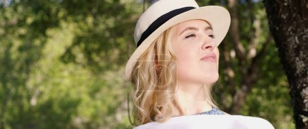 Portrait of the young woman in a hat on warm sunny day