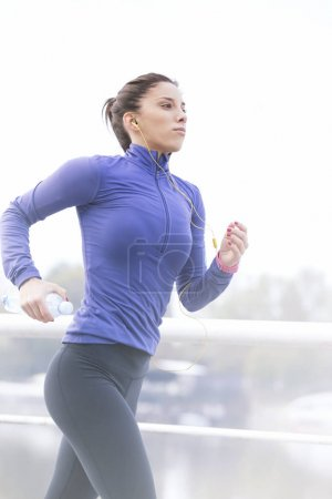 Female runner jogging and listening to music