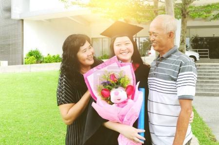 Asian university student and family celebrating gr...