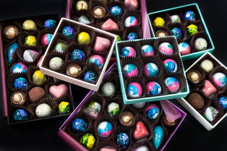 Chocolate handmade candy sweets in a gift boxes. Black background.