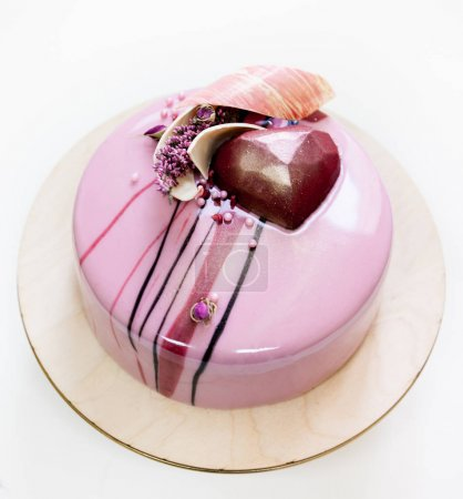 Minimalistic pink mousse cake with coated with mirror glaze on a white background. Chocolate heart, chocolate swirl and dry heather decor.