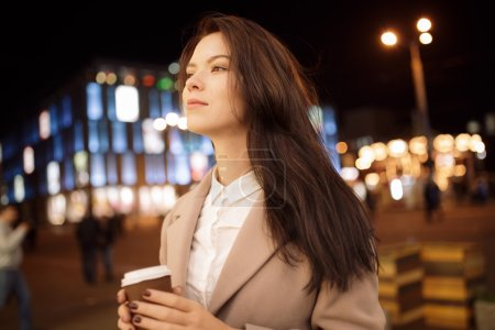 Woman walking in night city and drinking hot aroma tea