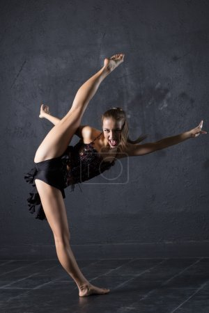Young professional dancer make a twine against textured wall background