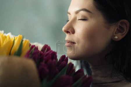 Closeup portrait of pretty women enjoying a nice smell of tulips bouquet