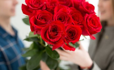 Cropped shot of unrecognizable boy gives bouquet of roses to girl in 8 march