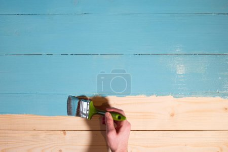 Man hand paints wooden board to blue color