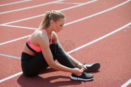 Sport woman athlete tie shoelaces sitting on stadium track