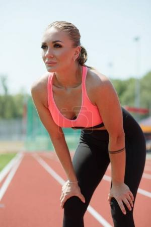 Photo for Young sporty woman sprinter athlete in sportswear resting after run on stadium track - Royalty Free Image