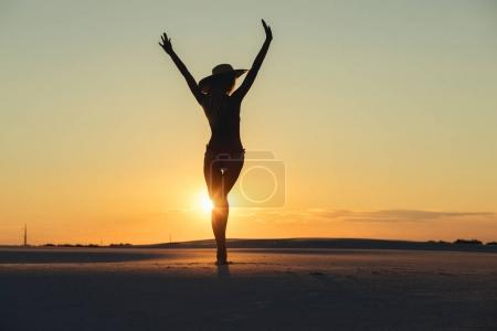 Photo for Silhouette of freedom woman with raised hands in gold desert at sunset - Royalty Free Image