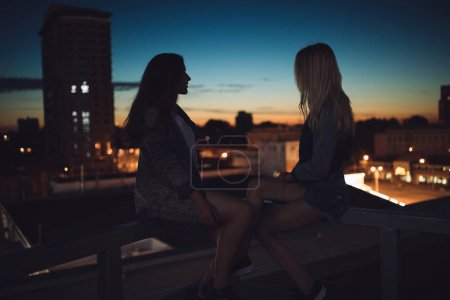 Photo for Silhouette of two young girl friends looks to evening dusk city scape - Royalty Free Image