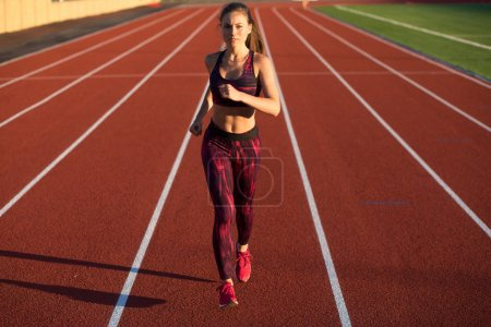 Photo for Professional sportswoman athlete sprinter running on stadium track in evening. Healthy lifestyle concept. Forward to the victory. - Royalty Free Image