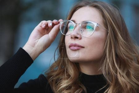 Photo pour Myopie, portrait en gros plan de la jeune étudiante en lunettes pour une bonne vision, fond bleu bâtiment - image libre de droit