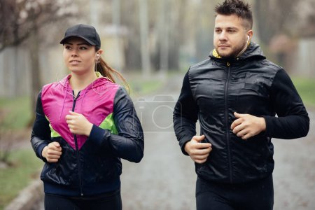 Two friends or couple jogging at the rainy day