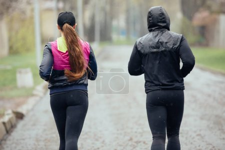 Two friends or couple jogging at the rainy day, rear view