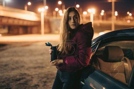 Portrait de femme conducteur tenant thermos bouteille penché sur la voiture, la nuit