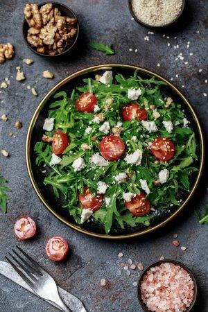 Photo pour Salade de légumes sains de roquette fraîche, tomates et noix sur assiette foncée. Menu diététique. Vue de dessus. Salade à la roquette - image libre de droit