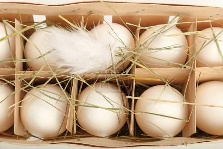 White chicken eggs in wooden container close up