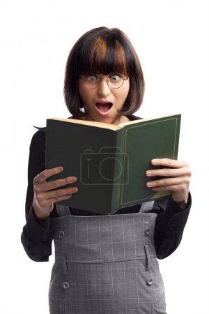 Shocked brunette schoolgirl looking in the book holding in her h