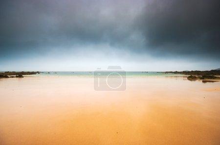 Empty beach and dark sky