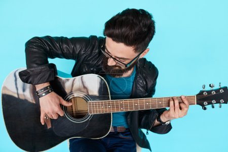 Close Bearded hipster man playing on acoustic guitar.