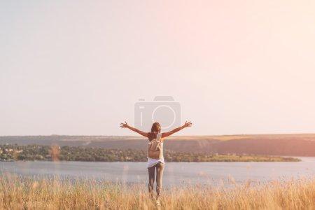 Beautiful girl in the meadow enjoying the sun