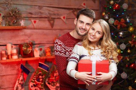 Happy couple with christmas gifts embracing at home.