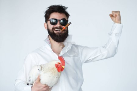 Photo for Crazy man smiling while holding chicken - Royalty Free Image