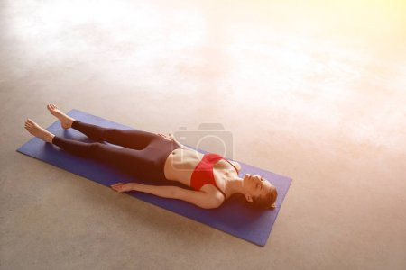 Photo for Above view of young woman working out in empty classroom, lying in Shavasana, resting after practice. Full length, top view - Royalty Free Image