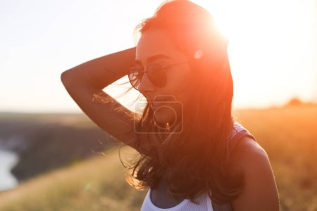 Beautiful young woman posing on a windy summer day