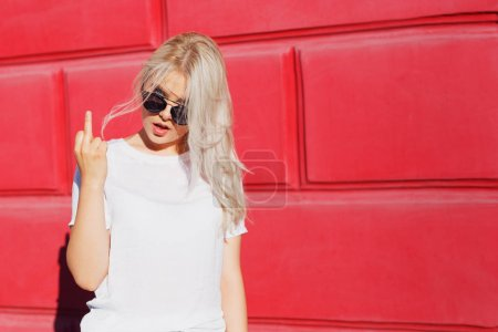 Photo for Teenage girl showing middle finger gesture. Rebel and crazy teen hipster in white t-shirt showing rude sign - Royalty Free Image