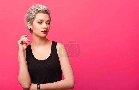Photo pour Belle femme avec des cheveux teints blonds courts et un maquillage propre regardant sur le côté sur fond de couleur rose avec espace de copie - image libre de droit