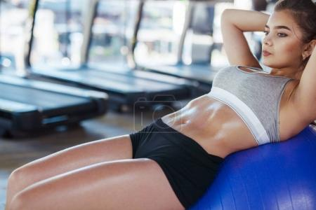 Photo for Young fit woman in sportswear lying on training ball doing abs exercise in gym. - Royalty Free Image