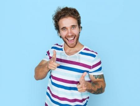 Photo pour Portrait de jeune homme décontracté tatoué pointant vers la caméra regardant amical sur fond bleu . - image libre de droit