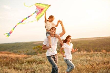 Photo pour Parents heureux et petite fille jouant avec cerf-volant coloré tout en s'amusant dans la prairie le jour ensoleillé - image libre de droit