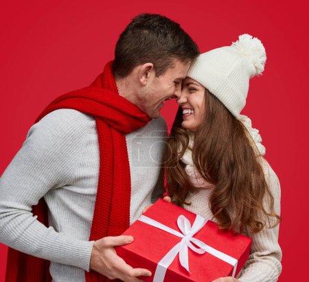 Foto de Hombre tierno dando regalo de Navidad en caja roja y besando a mujer encantadora en sombrero blanco sonriendo con los ojos cerrados - Imagen libre de derechos