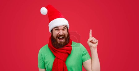 Photo for Happy bearded man in elf costume looking at camera and pointing up during Christmas celebration against red background - Royalty Free Image