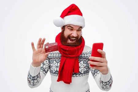 Photo pour Homme barbu excité à Santa Hat et écharpe montrant sa carte de crédit et payant ses achats en ligne lors de ses achats de Noël sur fond blanc - image libre de droit