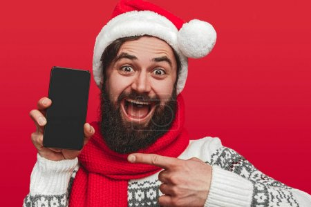 Photo for Excited bearded male in Santa hat pointing at smartphone with blank screen and looking at camera while showing Christmas app against red background - Royalty Free Image