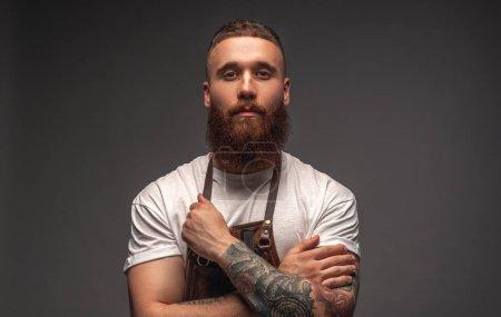 Photo pour Focalisé mâle barbu avec des bras tatoués regardant la caméra et ajustant la bande de tablier tout en travaillant dans le salon sur fond gris - image libre de droit