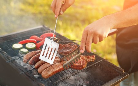 Photo for Unrecognizable man using tongs and spatula to turn delicious sausages on grill near meat and vegetables while cooking in countryside - Royalty Free Image